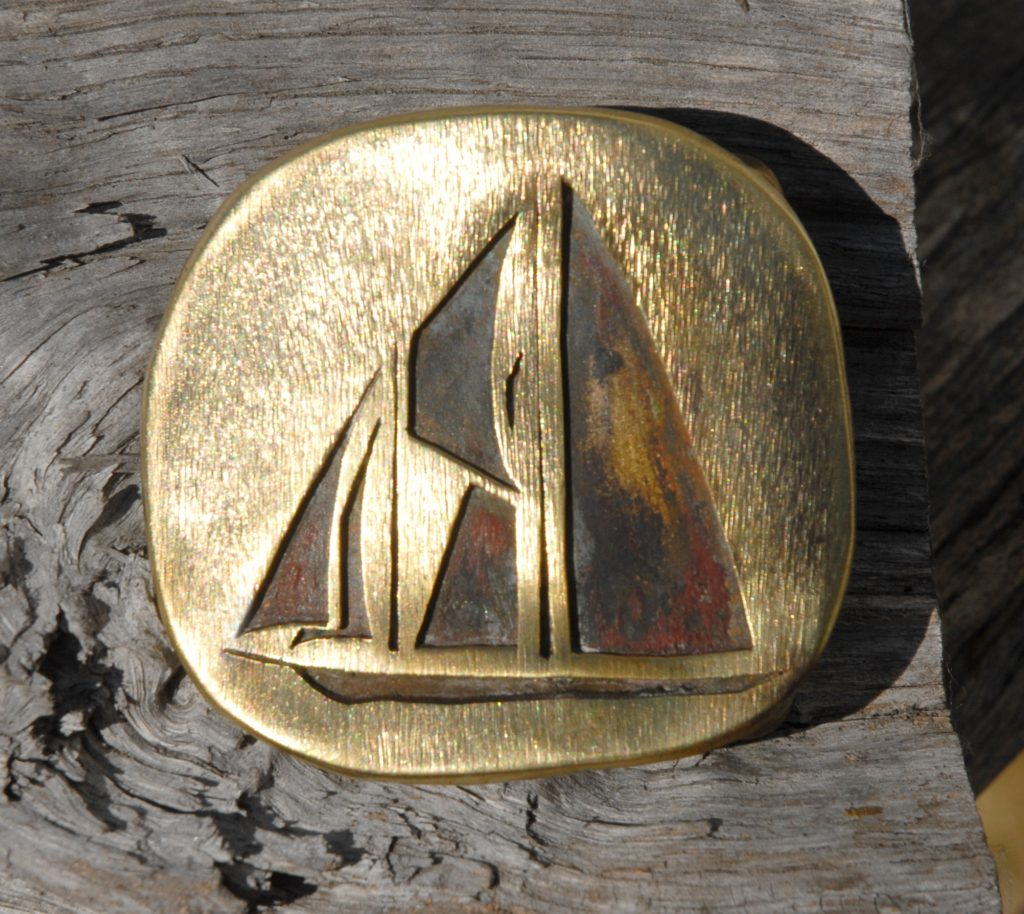 photo of a brass belt buckle depicting a topsail schooner sailboat