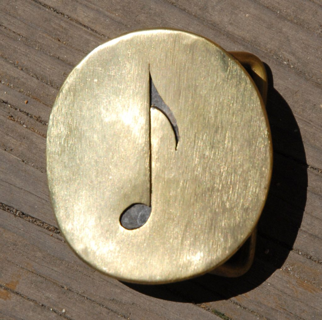 photo of a brass belt buckle depicting a musical eighth note