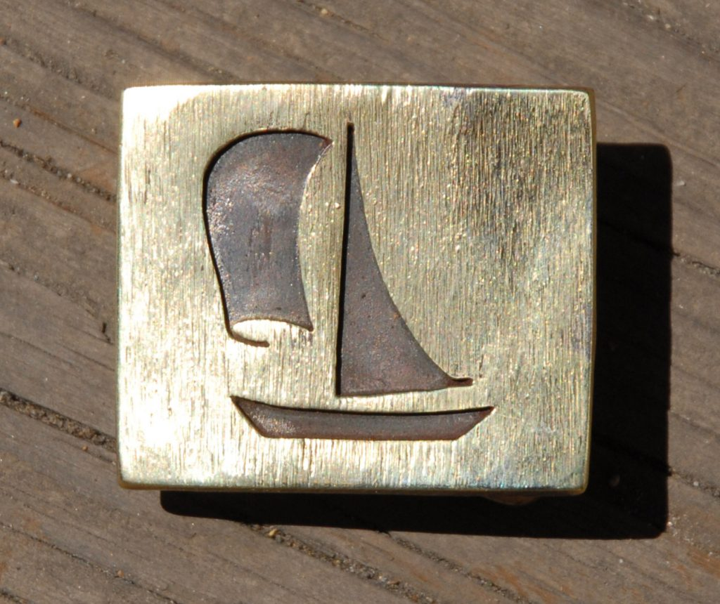 photo of brass belt buckle depicting a sailboat with spinnaker sail