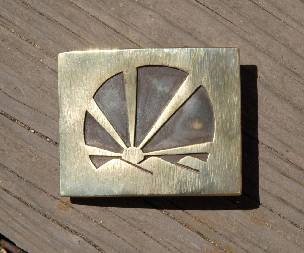 photo of a brass belt buckle depicting a sunset over a line of hills