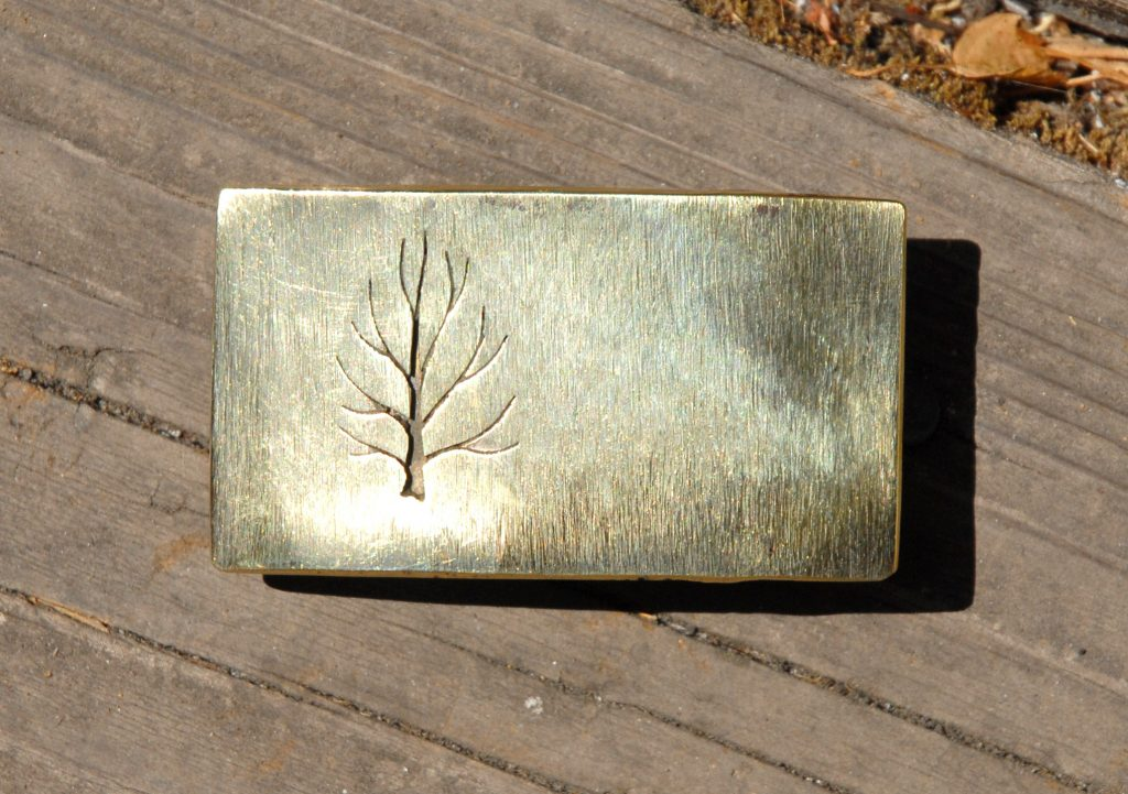 photo of a brass belt buckle depicting a leafless tree